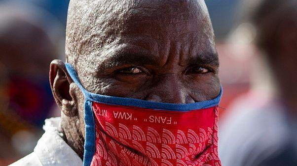 Um homem proteje-se da epidemia em Tembisa, Joanesburgo, África do Sul