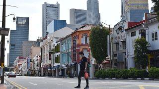 Un hombre con una mascarilla cruza la calle en el distrito de Chinatown de Singapur el martes 12 de mayo de 2020.