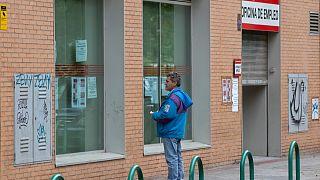 Un homme regarde des annonces d'emploi sur la vitrine d'une agence pour l'emploi à Madrid en Espagne