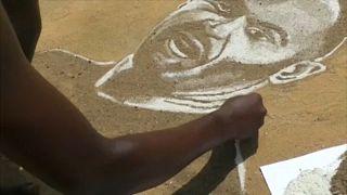 Он рисует футболистов на песке