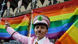 A participant gestures with a rainbow flag under the portraits of Hungarian politicans during the gay rights Pride Parade in Budapest (Photo by PETER KOHALMI / AFP)