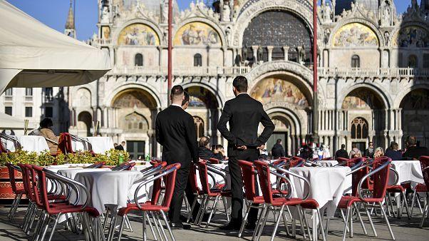 Dos camareros esperan a los clientes en un restaurante de la Plaza de San Marcos el 28 de febrero de 2020 en Venecia, Italia.