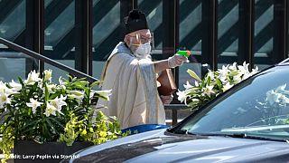 کشیش با تفنگ آبپاش مومنان را برکت میدهد
