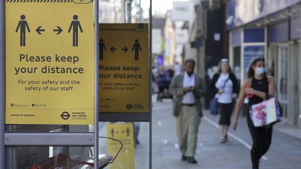 Signs advise people to social distance on a bus stop along a high street, in London