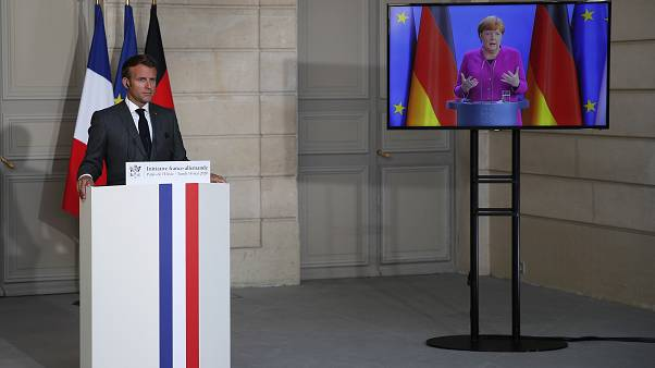 French President Emmanuel Macron listens to German Chancellor Angela Merkel during a joint video press conference Monday, May 18, 2020 in Paris. (AP/Francois Mori, Pool)