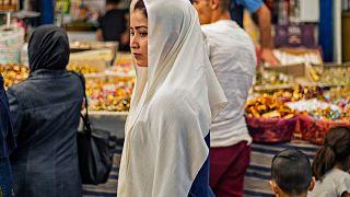 شابة سورية تسير وسط السوق المركزي في القامشلي بمحافظة الحسكة. 19/05/2020