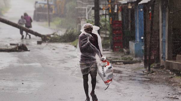 A man covers himself with a plastic sheet and walks in the rain ahead of Cyclone Amphan landfall