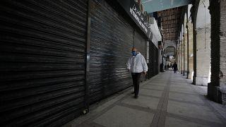 رجل يمشي قرب محلات تجارية في العاصمة الجزائر - 2020/04/29