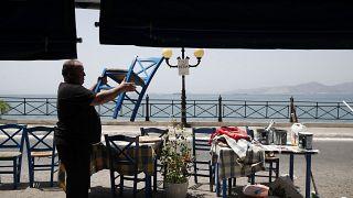 Un trabajador coloca sillas en un restaurante de pescado antes de su reapertura en el Pireo.