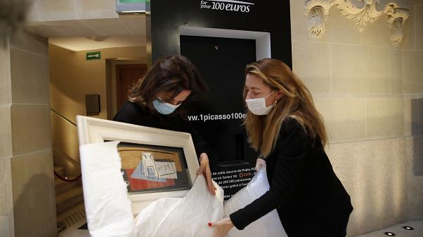 "Raffle organizers Peri Cochin, left, and Arabenne Reille unbox the painting ""Nature morte"" by Picasso at Christie's auction house, Tuesday, May 19, 2020 in Paris"