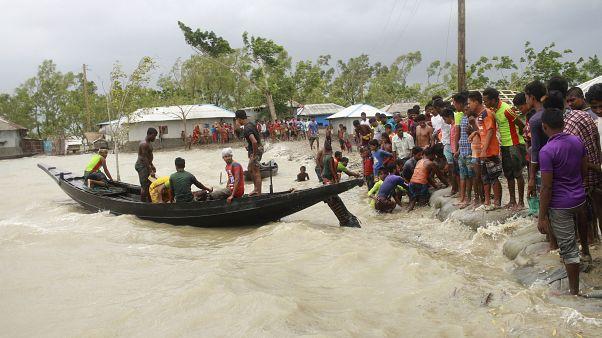 A boat brings people to land, as locals check an embankment before Cyclone Amphan made landfall, in Shyamnagar, Shatkhira, Bangladesh.