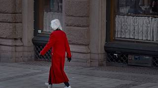 La gente beve al bar, mentre una donna anziana passa per strada a Stoccolma, Svezia