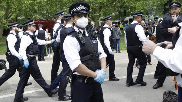 A police officer wears a face mask during a mass gathering protest organised by the group called 'UK Freedom Movement', in Hyde Park in London