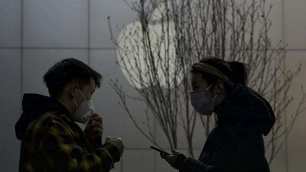 Masked shoppers stand near the Apple logo in Beijing