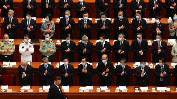 I delegati applaudono l'arrivo del Presidente Xi Jinping al Congresso Nazionale del Popolo cinese, a Pechino