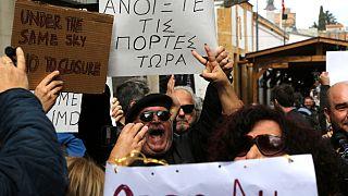 """متظاهرون يطالبون بفتح نقطة عبور بين شطري قبرص، حاملين لافتات كتب عليها باليونانية """"افتح الأبواب الآن"""" 29/02/2020"""