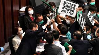 Hong Kong pro-democracy lawmakers holding up placards are blocked by security as they protest during a meeting chaired by pro-Beijing lawmakers on May 22, 2020