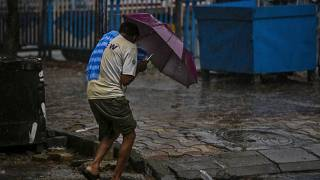 A man struggles to hold his umbrella and walk against high wind in Kolkata, India, Wednesday, May 20, 2020.