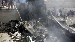Des pompiers finissent d'éteindre l'incendie provoqué par la chute d'un avion sur Karachi - Pakistan - le 22 mai 2020