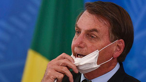 Brazil's President Jair Bolsonaro removes his mask to speak at a press conference on the new coronavirus in Brasilia, Brazil, March 18, 2020