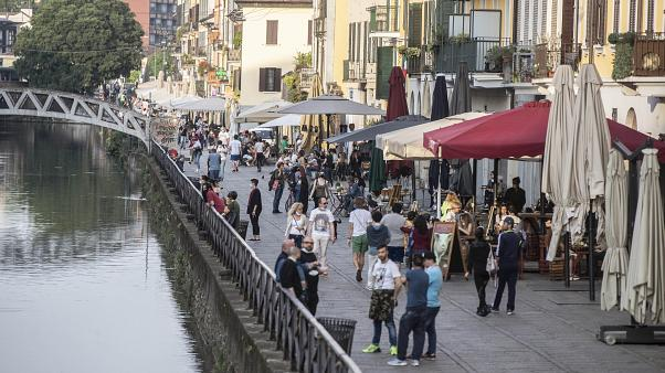 People walk along the Naviglio grande canal in Milan, Italy, Monday, May 18, 2020