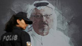 Wednesday, Oct. 2, 2019 file photo, a Turkish police officer walks past a picture of slain Saudi journalist Jamal Khashoggi near the Saudi Arabia consulate in Istanbul