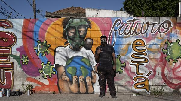 Graffiti artist Angelo Campos poses for a photo by his mural referencing the COVID-19 pandemic which he said he painted in honor of health workers in Rio de Janeiro, Brazil