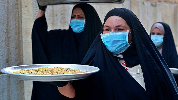 Iraqi women carry cookies for the upcoming Muslim Eid al-Fitr celebrations that mark the end of th