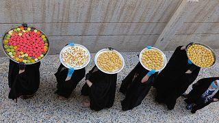 سيدات عراقيات يحملن على رؤوسهن بمدينة البصرة حلوى عيد الفطر الموافق ليوم غد الأحد 22/05/2020