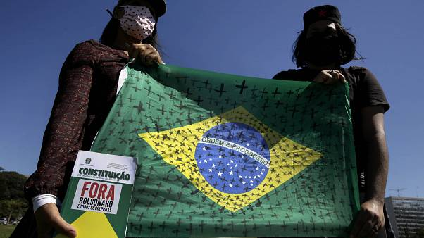 Demonstrators hold a national flag marked with black crosses during a protest demanding President Jair Bolsonaro be impeached
