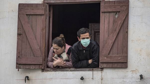مغربيان يطلان من نافذة بيتهما في الرباط - 2020/04/09