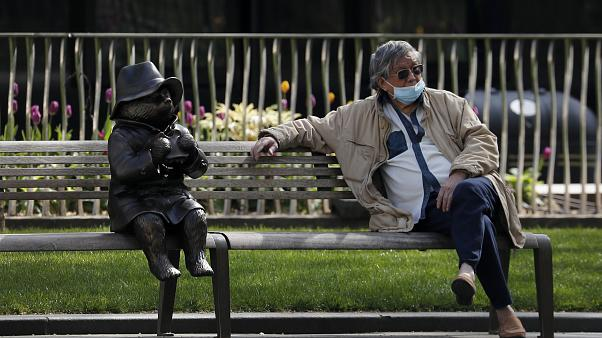 A man relaxes on a bench in London, next to a sculpture of Paddington Bear, as the country is in lockdown to help curb the spread of the coronavirus, Wednesday, April 15, 2020