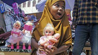 طفلة صومالية تحمل لعبة اشترتها بمناسبة العيد، مقديشيو الصومال.