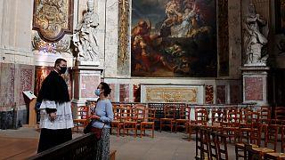 Un prêtre parle avec une croyante avant une message en l'église Saint Roch à Paris, le 23 mai 2020