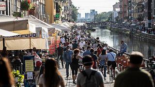 Des promeneurs profitent du soleil le long du canal Naviglio Grande à Milan le 24 mai 2020