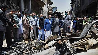 Provincial governor Imran Ismail, center, in blue coat, and Pakistan's aviation minister Ghulam Sarwar, center in black waistcoat, visit the site of Friday's plane crash
