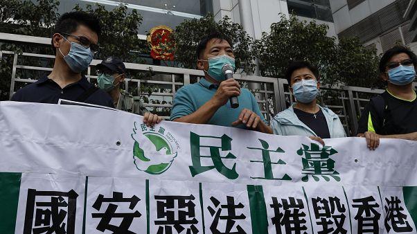 أعضاء الحزب الديمقراطي يحملون لافتات خلال احتجاج أمام مكتب الحكومة المركزية الصينية في هونغ كونغ.