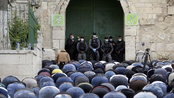 مصلون فلسطينيون ساجدون عند باب الأسباط المؤدي للمسجد الأقصى المغلق بسبب كورونا وأمامهم عناصر من القوات الخاصة في الشرطة الإسرائيلية
