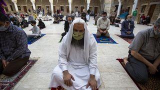 Musulmanes con máscaras faciales asisten a las oraciones de Eid al-Fitr fuera de una mezquita en la ciudad de Gaza, el 24 de mayo de 2020.