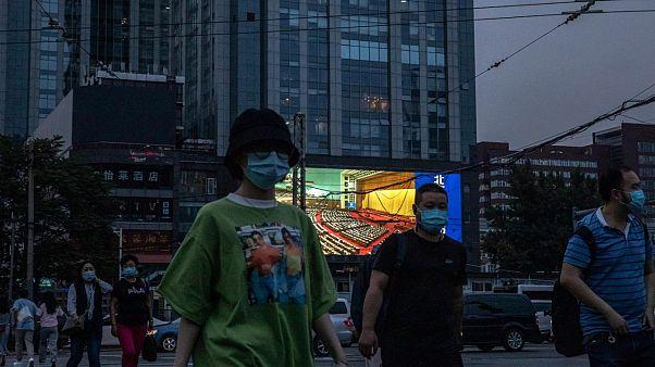 Des personnes marchent dans la rue alors qu'un écran géant diffuse des images du congrès national, Pékin le 22 mai 2020