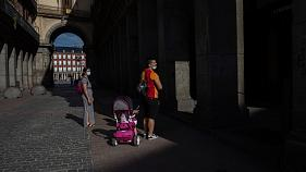 A family walks in downtown Madrid, Spain, Sunday, May 24, 2020. Spain is preparing to reopen some of its beaches for sunbathing on Monday