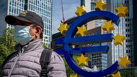 A man walks by the Euro sculpture in front of the old the European Central Bank in Frankfurt, Germany, Tuesday, May 5, 2020.