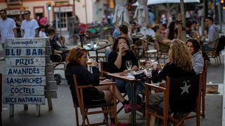 People drink as they sit on a terrace in Barcelona on Monday, May 25