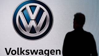 n this Wednesday, Nov. 28, 2018 file photo an attendee waits for the start of a news conference at the Volkswagen booth at the Los Angeles Auto Show.