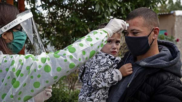 A health worker takes the temperature to a resident of Altos de San Lorenzo neighbourhood, near the city of La Plata, Argentina