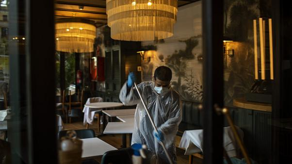 A worker cleans a restaurant ahead of the opening on Monday, May 25, 2020 in Barcelona, Spain.