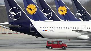German Lufthansa planes sit parked in a line at the airport in Munich