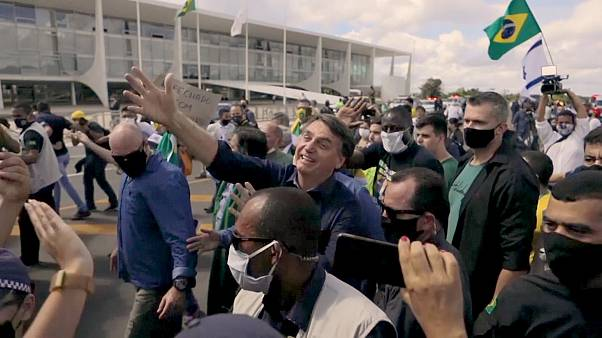 Despite virus surge, President Jair Bolsonaro greets his supporters without a face mask.