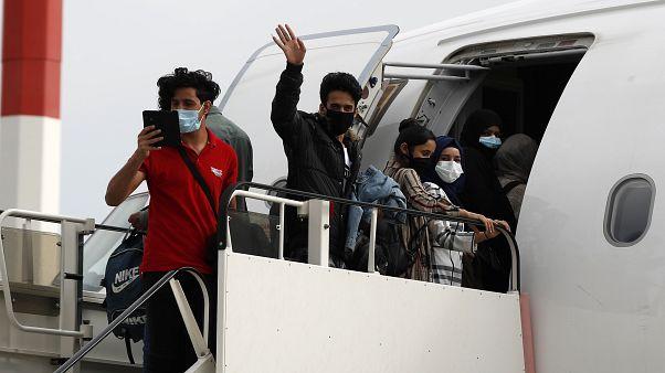 مهاجرون قصر يصعدون إلى الطائرة المقرر أن تقلهم من اليونان إلى ألمانيا