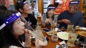 يابانيون يجلسون في حانة يرتدون أقنعة بلاستيكية يشبه الدرع الذي يغطي الوجه في اوساكا غرب اليابان 25/05/2020